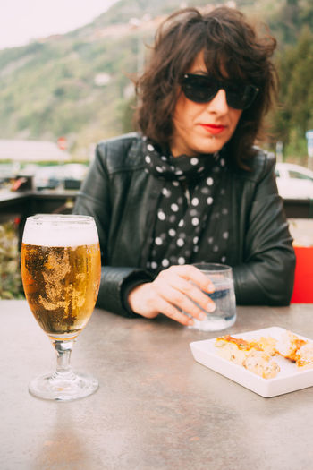 Portrait Of Mid Adult Woman Sitting By Beer Glass On Table