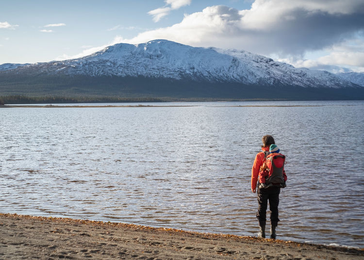 Hiker carrying child in backpack standing at the shore facing a snow capped mountain