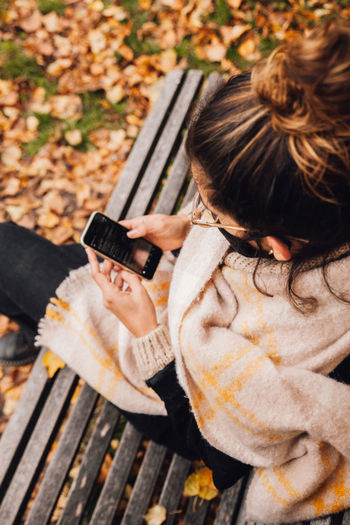 High angle view of girl holding mobile phone while sitting outdoors