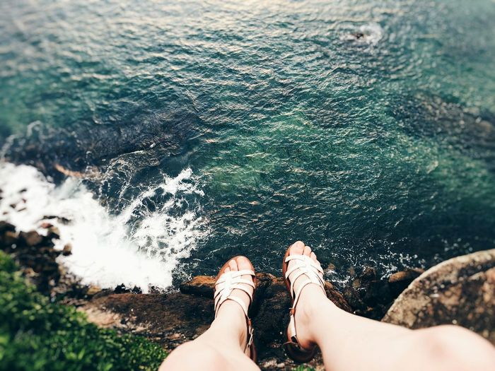 Low section of woman dangling legs over sea