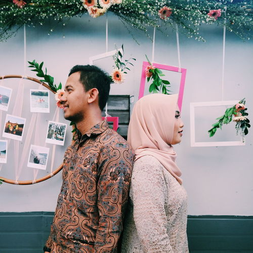 Smiling couple standing against decoration