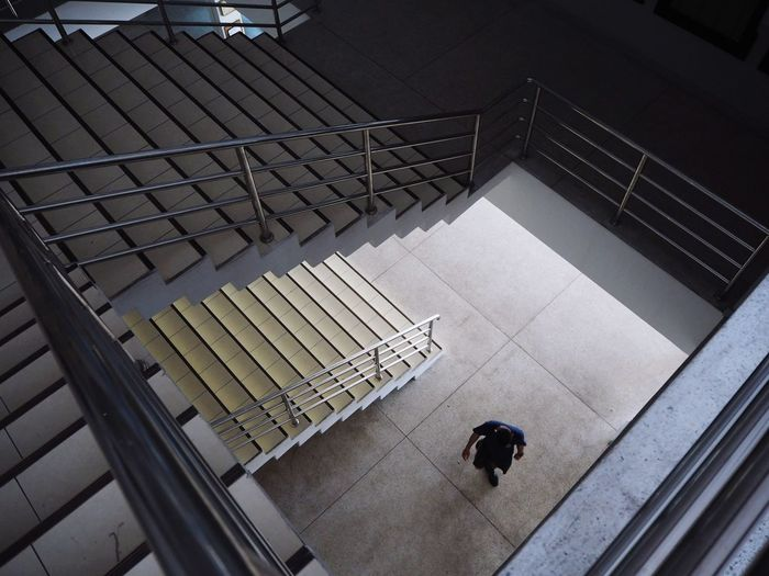 High angle view of person walking on staircase in building