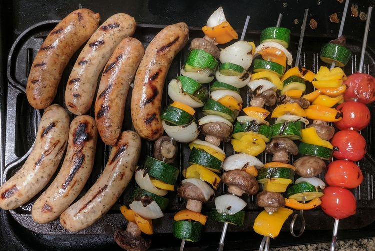 Chicken sausages and vegetable kebabs on the grill