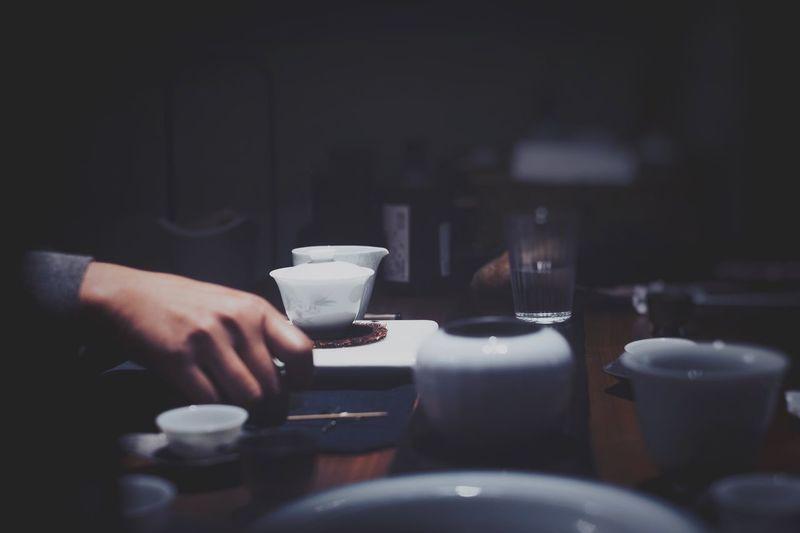 Cropped hand of man holding kitchen utensil in darkroom