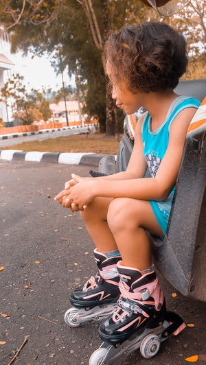 a short break, after playing roller skates Full Length Sitting One Person Child Day Women Girls Leisure Activity Real People Childhood Casual Clothing Lifestyles Females Hairstyle Shoe Looking Curly Hair City Outdoors Innocence
