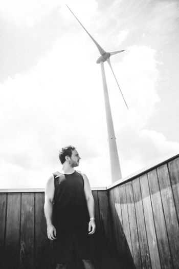 Man standing on wind turbine against sky thinking about life