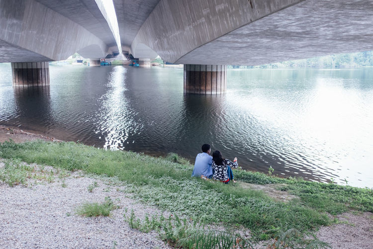 Couple sitting below bridge