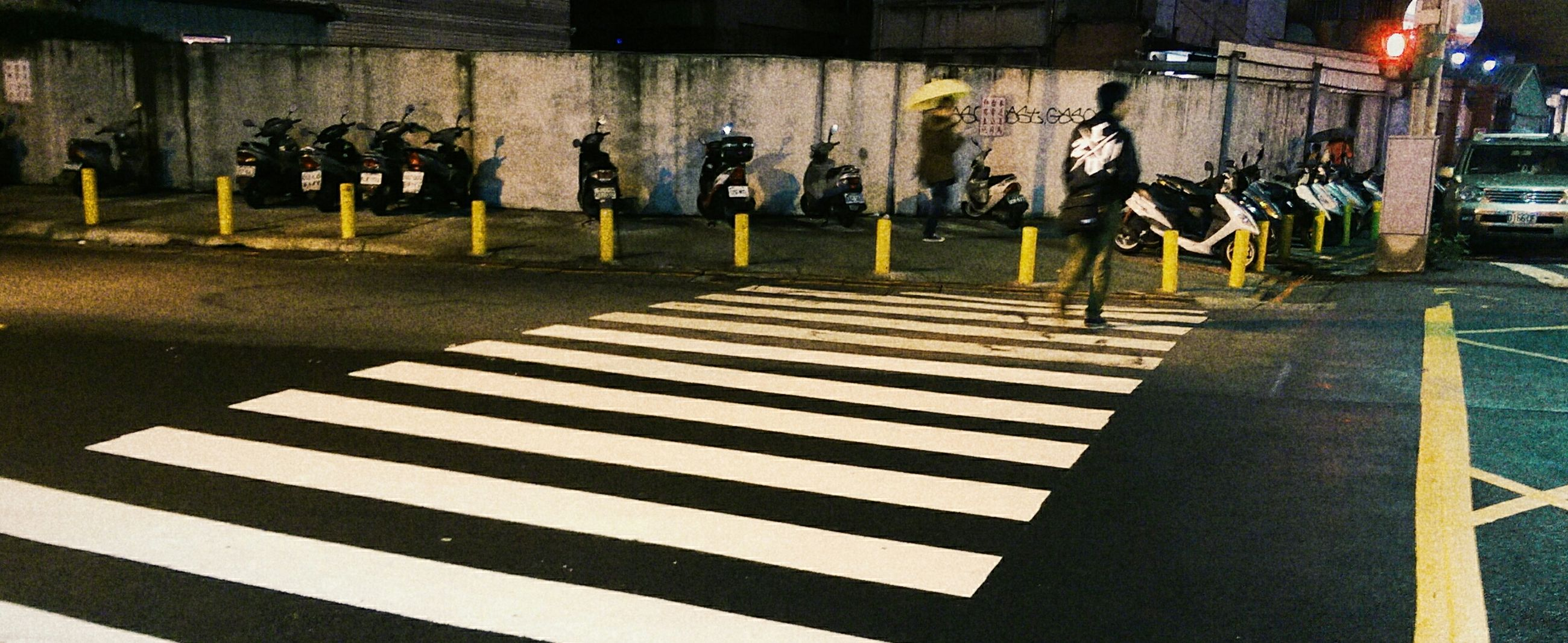 street, road marking, transportation, road, night, city street, zebra crossing, city, sidewalk, in a row, the way forward, incidental people, illuminated, land vehicle, outdoors, city life, street light, shadow, car, built structure