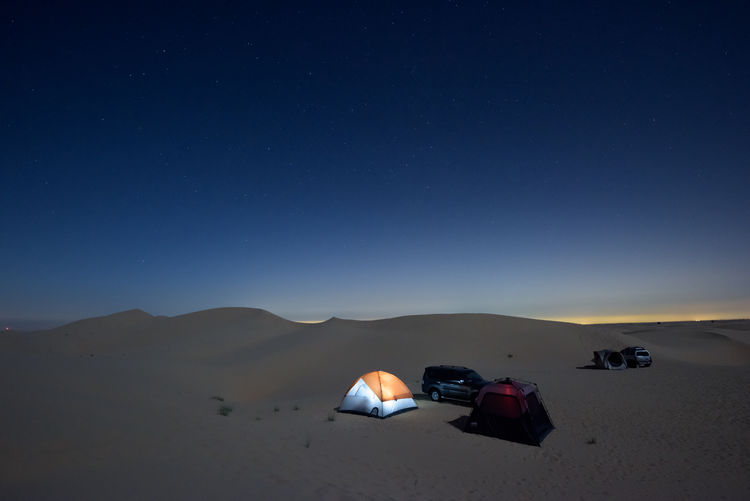 Camping under the stars in the desert Camping Deserts Around The World Arid Climate Beauty In Nature Blue Car Climate Desert Environment Illuminated Land Land Vehicle Landscape Mode Of Transportation Motor Vehicle Nature Night Night View No People Scenics - Nature Sky Stars Tranquil Scene Tranquility Transportation