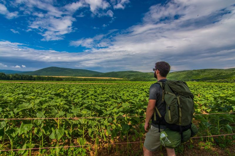 Male Hiker Looking At Farm While Standing Against Cloudy Sky
