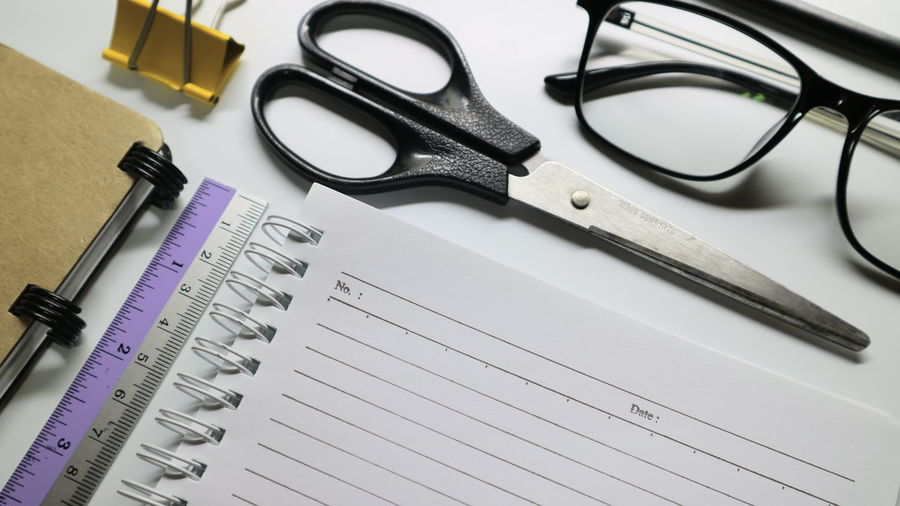 High angle view of scissors and eyeglasses with ruler on book