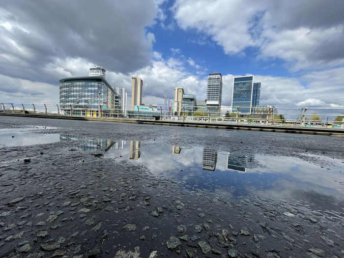 Reflection of buildings in puddle on river