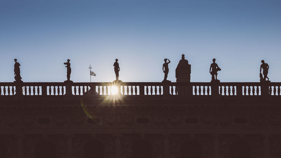Silhouette people against clear sky