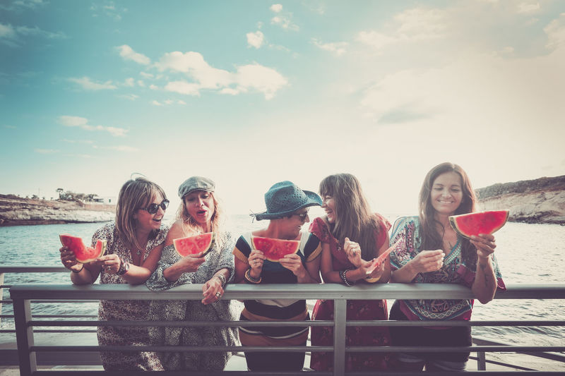Women eating watermelon slice while standing by railing against sky