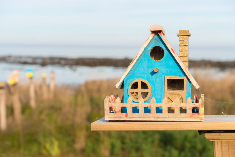Close-up of wooden birdhouse over field