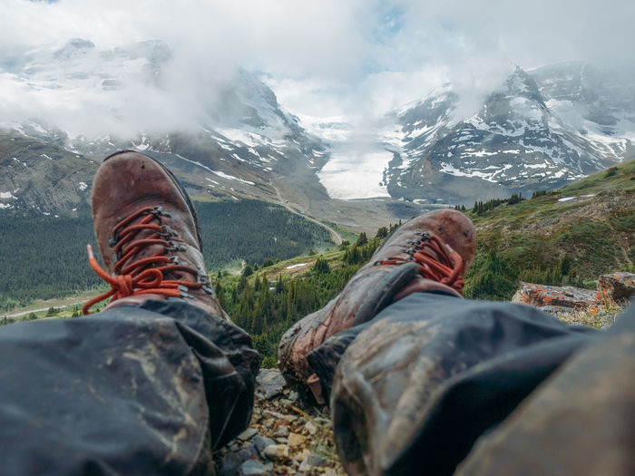 Low section of hiker sitting on cliff against snowcapped mountains