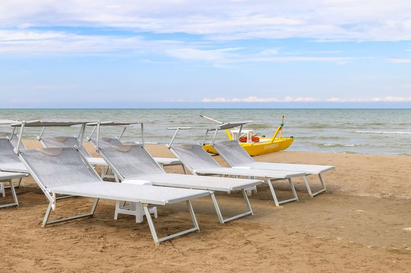 Gray sunbeds on the beach, Italy, Riccione Italy. Riccione Italy Emiliaromagna Rimini Riccione Resort Emergency Equipment Rescue Boat Gray Chaise Lounge Sunbed Sea Beach Sand Water Horizon Over Water Shore Sky Chair Tranquil Scene No People Summer Outdoors Day Vacations