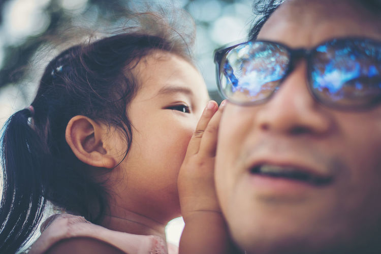 Close-up of daughter whispering in ear of father