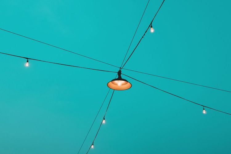 Low angle view of illuminated lights against clear blue sky