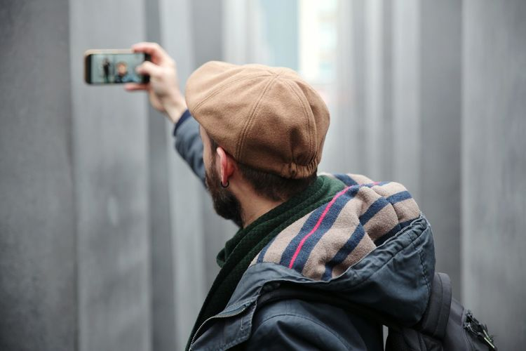 Side View Of Man Taking Selfie Against Wall