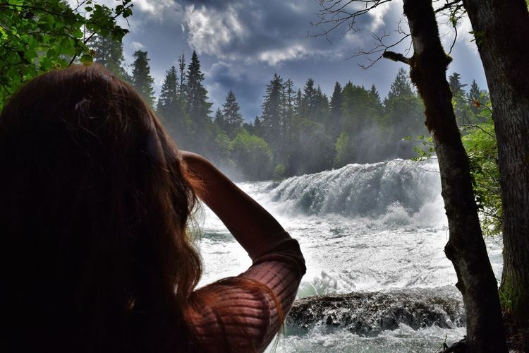 Rear view of woman looking at waterfall in rainforest