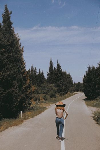 Rear view of woman standing on road by trees against sky