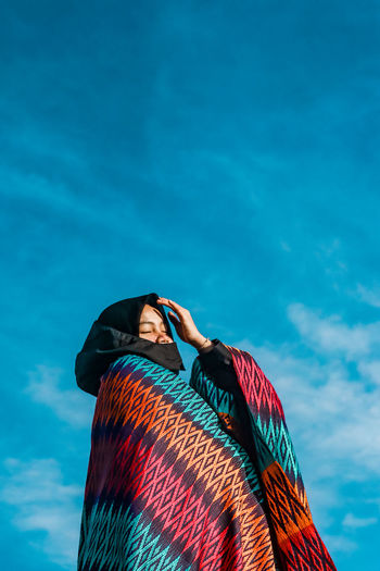 Low angle view of woman wearing hijab standing against blue sky