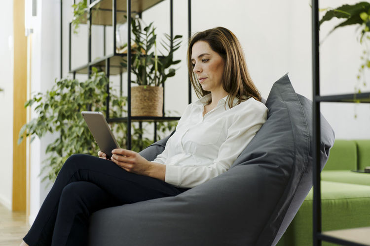Young woman using phone while sitting on chair