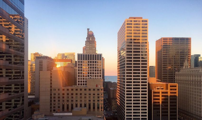 Modern buildings against clear sky in city during sunset
