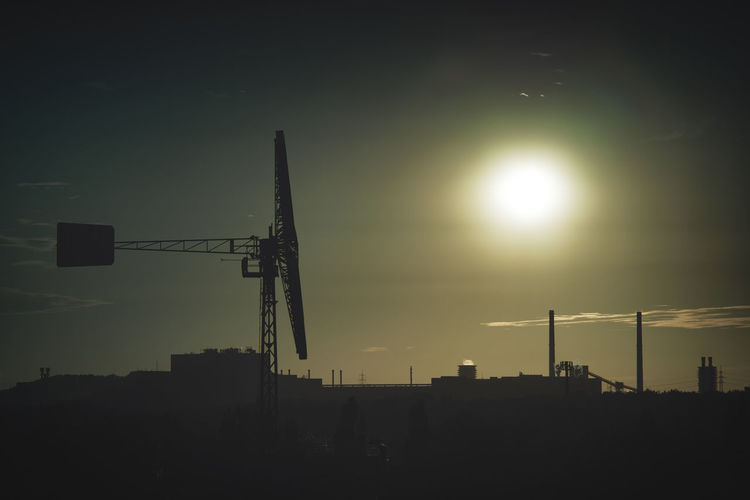 Silhouette cranes at construction site against sky during sunset