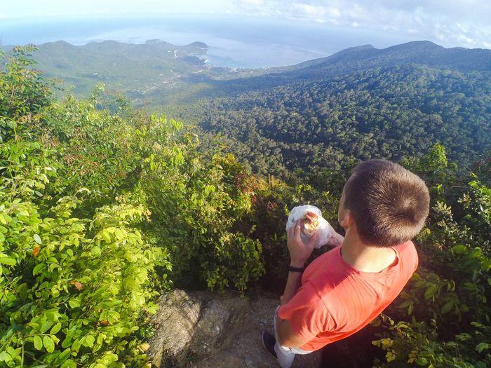 High angle view of man on rock looking at ko pha ngan