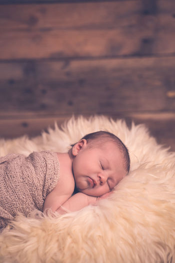 Portrait of cute baby sleeping on bed