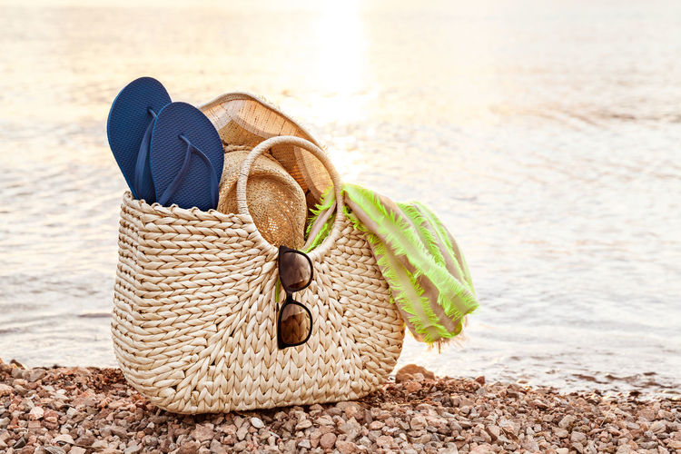 Straw Bag, Hat, Sunglasses And Flip Flops On The Shore At Sunset In The Summer Fashion Horizontal Recreation  Bag Beach Candid Flip-flop Hat Holiday Lake Leisure Activity Nature No People Outdoors Relaxation Sandal Scarf Shoe Summer Sun Hat Sunglasses Sunlight Sunset Vacations Water