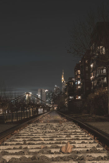 Illuminated railroad tracks by buildings against sky at night