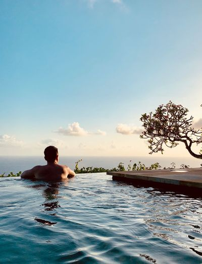 Rear view of man in infinity pool against sky during sunset