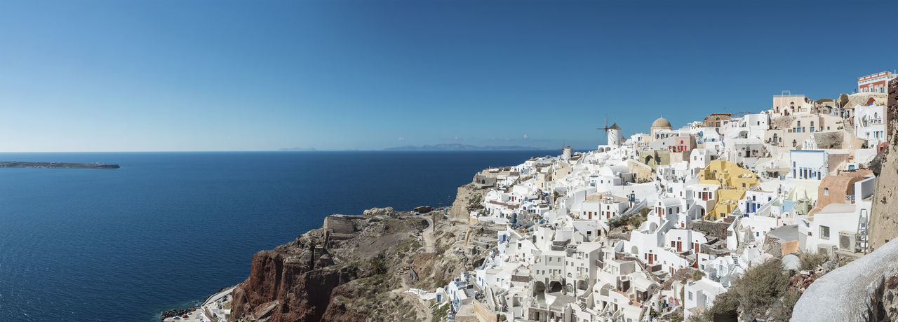 Panoramic View With Iconic Windmills Of Santorini Caldera Greek Panorama Architecture Blue Built Structure Clear Sky Cliff Day Greece Horizon Horizon Over Water Nature No People Oia Santorini Scenics - Nature Sea Sky Water