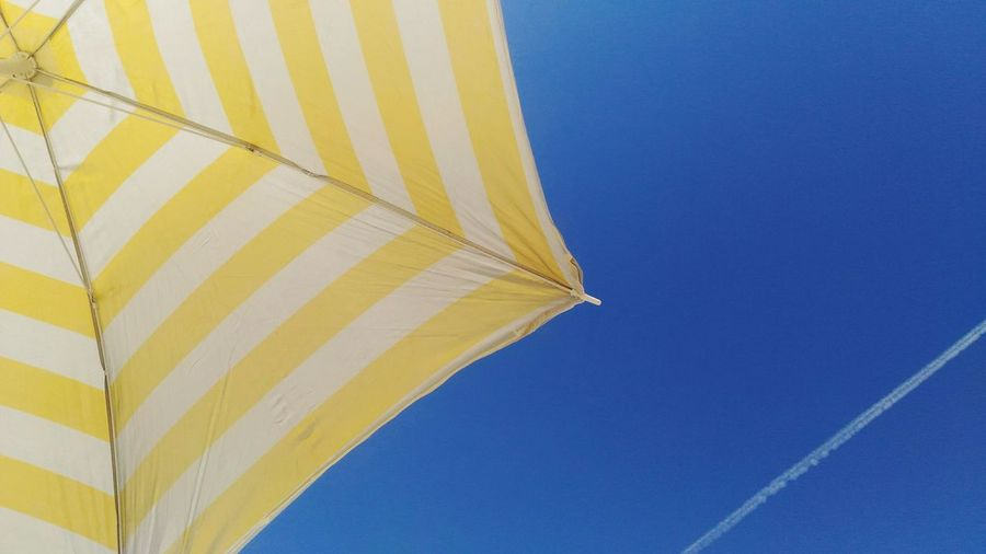 Cropped Image Of Striped Beach Umbrella Against Blue Sky With Vapor Trail
