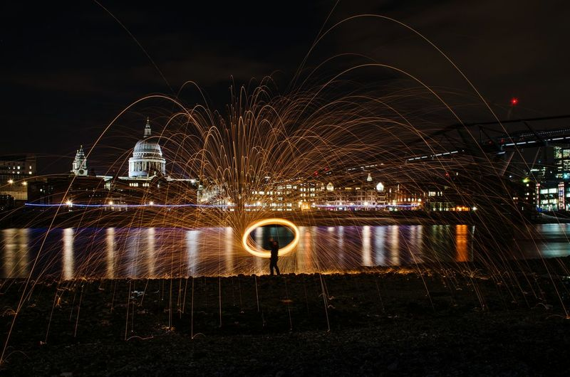 Man performing wire wool against st pauls cathedral at night