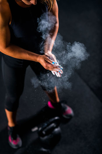 Athlete applying powder on hand while standing by weights