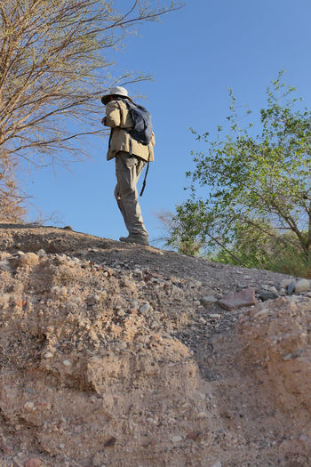 Low angle view of man standing on rock against sky