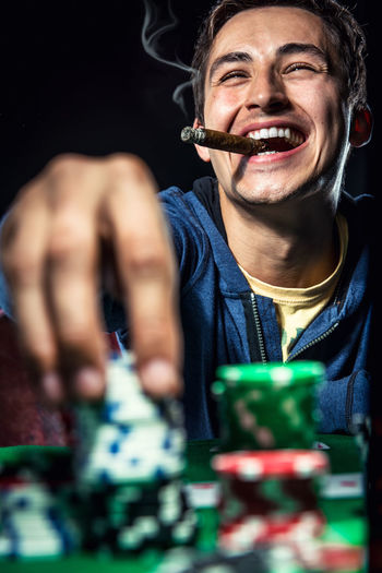 Smiling Man Playing Poker With Cigar Against Black Background