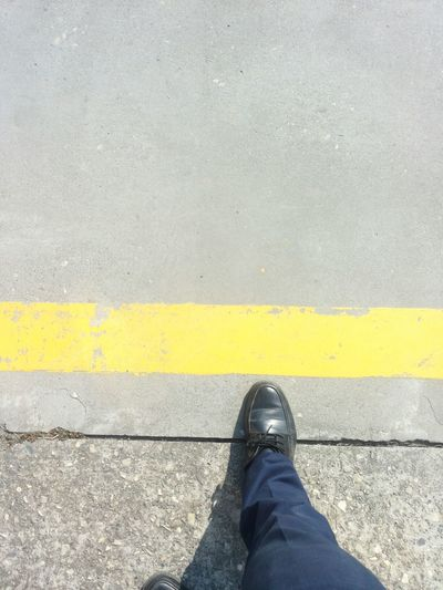 Do not cross the yellow line Low Section Shoe Human Leg Yellow One Person Human Body Part Standing Real People Personal Perspective Unrecognizable Person Men Road Lifestyles Day Outdoors Leisure Activity One Man Only Close-up People Adult Flying High The City Light Adapted To The City The Next Step Yellow Line