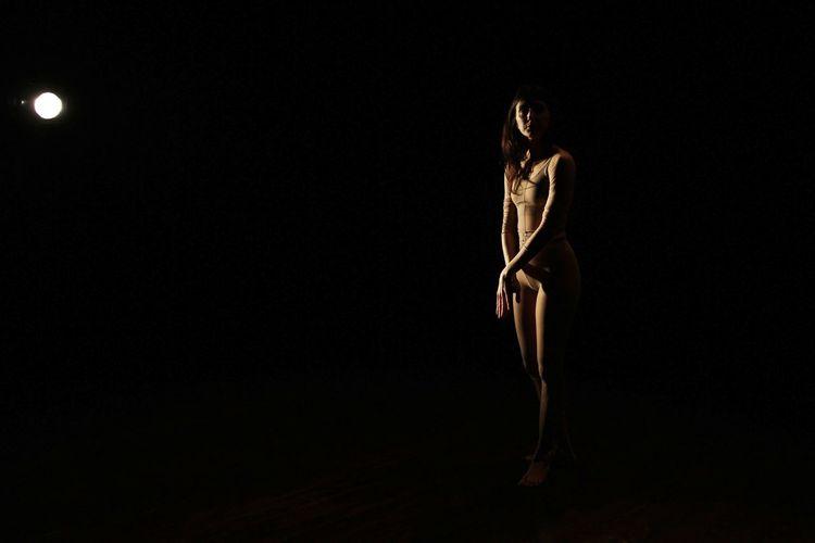 Woman Standing By Illuminated Light Bulb