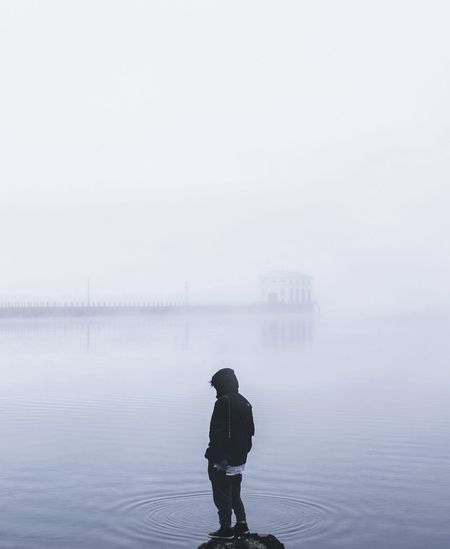 Rear View Of Person Standing In Lake During Foggy Weather