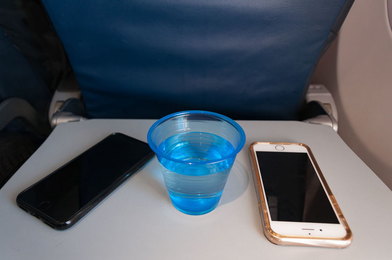 Breaktime Vacation Time Airplane Wing Cell Phones Cup Of Water Leisure Activity Leisure Time Old Cellphones Phone Phones Water