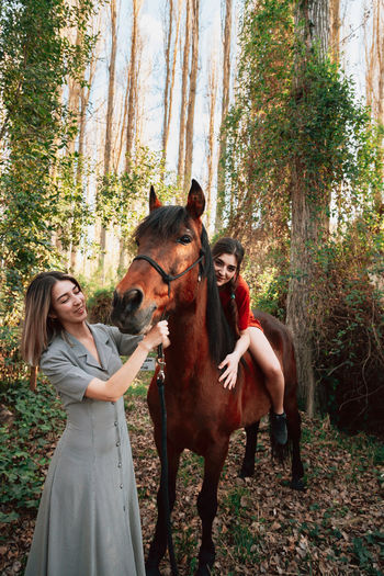 Two women friends chatting and taking a ride with their horse through the countryside