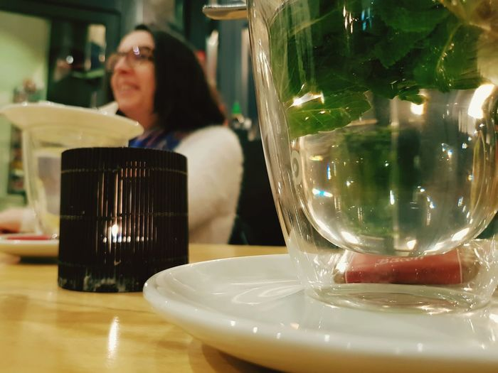 Woman sitting at glass table in restaurant