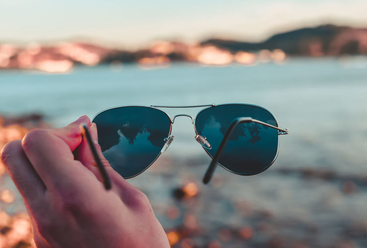 Close-up of hand holding sunglasses against sky at beach