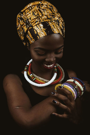 Black Woman Portrait Headwrap  Accessories African Fabric African Accessories Beautiful Woman Child Childhood Front View Indoors  One Person Lifestyles Black Background Leisure Activity Real People Innocence Girls Cute Studio Shot Holding Woman Smiling Happy Nails Nail Polish Looking Down