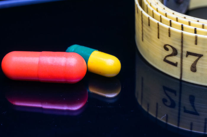 colorful of a medication and measurement tape isolated on black Diet Isolated Reflection Antibiotic Background Black Capsule Close-up Colorful Concept Day Healthcare And Medicine Healthy Indoors  Measurement Tape Medication Medications Medicine Multi Colored No People Nutritional Supplement Pill Prescription Medicine